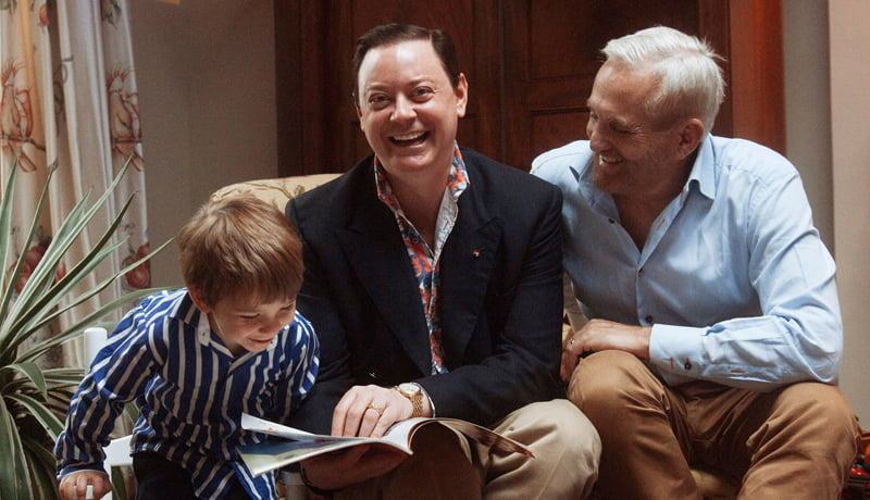 Frame do filme Longe da Árvore. Na imagem, Andrew Solomon está sentado em um sofá ao lado de uma criança e um senhor. Eles folheiam um livro sorrindo.