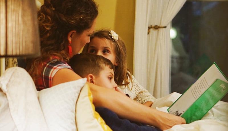 Foto de adulto lendo um livro para duas crianças. Representa o vínculo entre eles