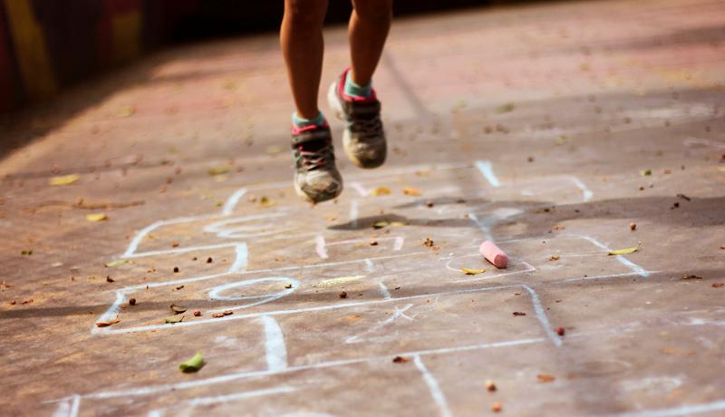 Foto de criança pulando amarelinha. Apenas os pés dela aparecem saltando na parte superior da imagem, No centro da foto está a amarelinha desenhada com giz no chão.