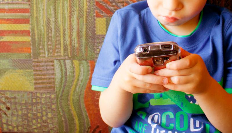 Foto de uma criança, localizada à direita da imagem, mexendo no celular. Ela veste uma camiseta azul com detalhes em verde. Ao fundo há um papel de parede com quadrados e listras verdes, vermelhas e marelas.