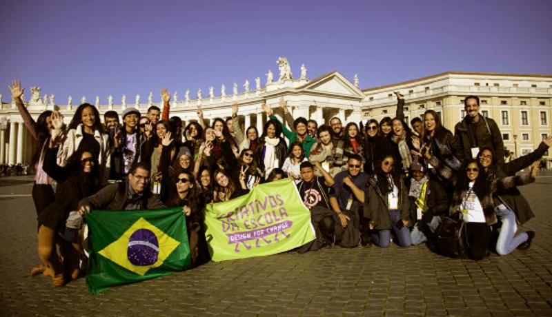 Foto e grupo de pessoas segurando a bandeira do Brasil e outra do Criativos da Escola. Ao fundo está o Coliseu.
