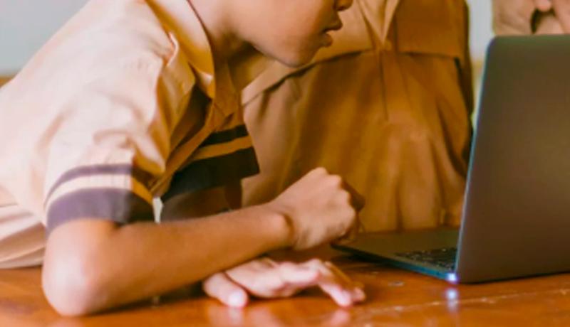 Foto de criança debruçada, de perfil, em uma mesa de madeira. Seu rosto está virado para um laptop que também repousa na mesa. Ao fundo, mais duas crianças observam o computador.