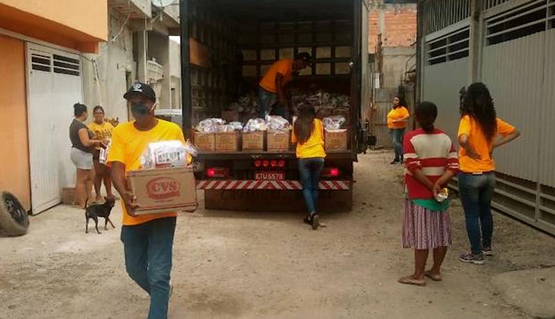 Pessoas distribuem em uma rua de terra cestas básicas para os moradores.