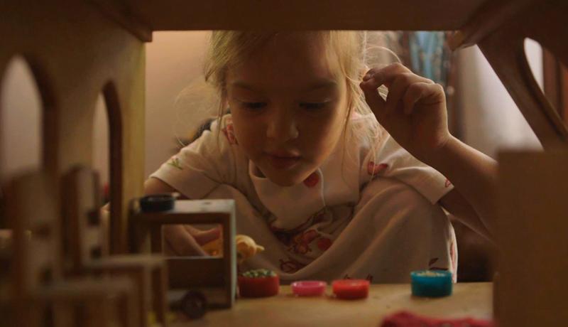 Em primeiro plano há o interior de uma casinha de boneca. Dentro dela tem cadeirinhas de madeira, um fogão e comidinhas. No vazado da construção aparece uma criança agachada, ela segura um boneco e interage com a casinha.