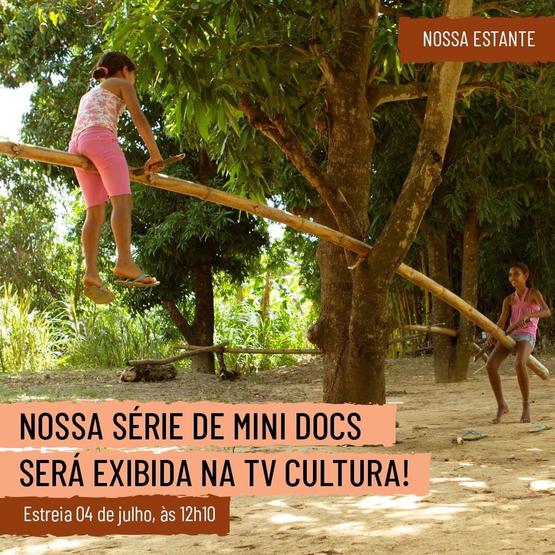 No centro da imagem há uma árvore. Entre os galhos mais baixos dela está atravessado um tronco de bambu. Em cada ponta do bambu está sentada uma criança como em uma gangorra. No canto superior direito está escrito sobre um retângulo marrom: