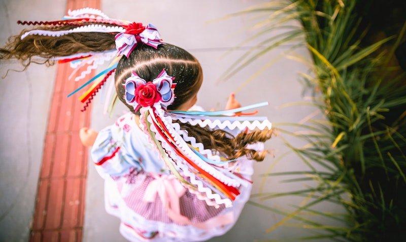 Imagem representando uma infância digna mostra menina dançando com roupa rosa de festa junina e maria chiquinhas