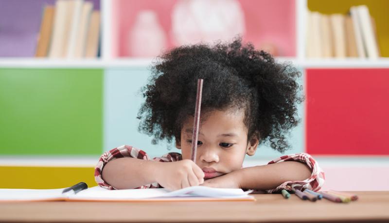 Criança escreve em um caderno apoiado sobre uma mesa.
