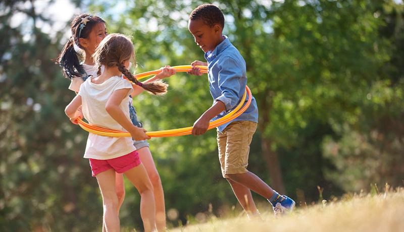 Foto representando o brincar mostra três crianças brincando com um bambolê
