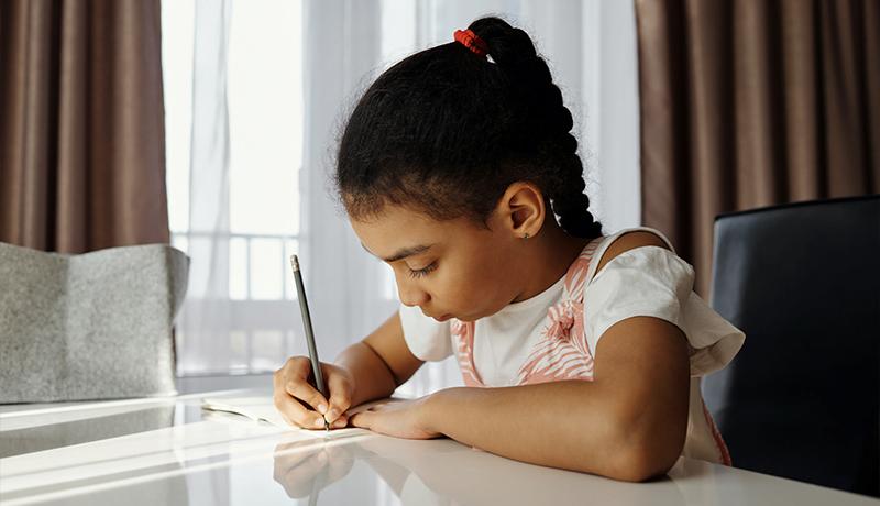 Foto mostra criança sozinha escrevendo em mesa em casa, representando o ensino domiciliar