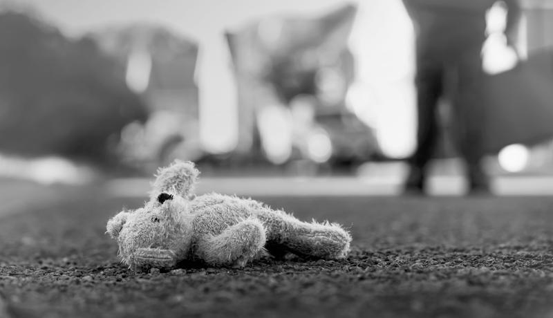 Foto em preto e branco de urso de pelúcia no chão.