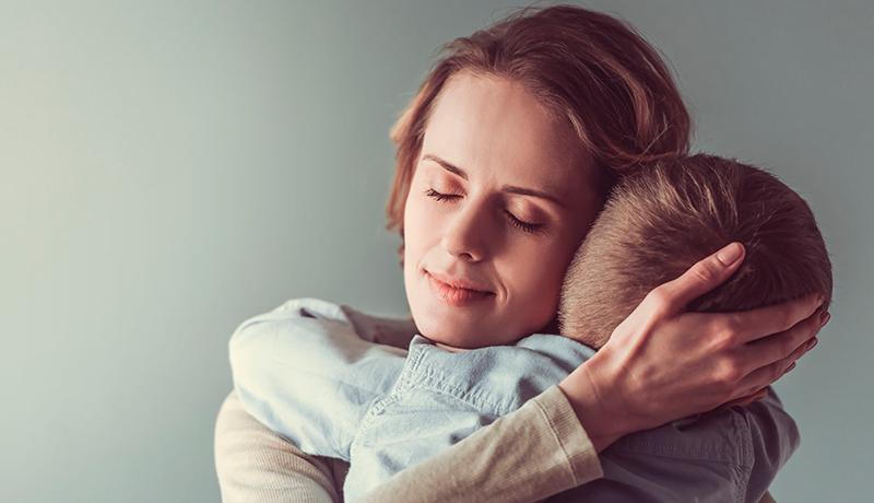 Foto mostra mãe abraçando criança