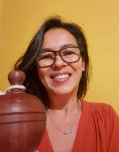 Foto mostra a pesquisadora Soraia Chung Saura sorrindo e, ao fundo, uma parede amarela