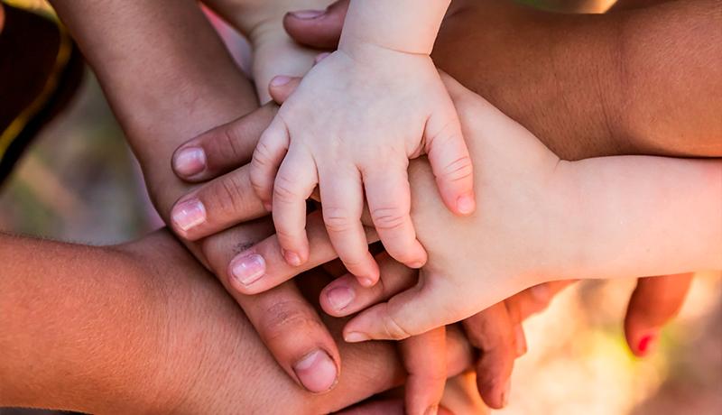 Foto de mãos de adultos e crianças sobrepostas, representando colaboração
