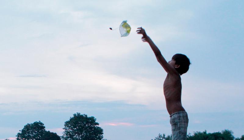 A foto que ilustra a nota pelo incêndio na escola Xukurank mostra criança indígena brincando com balão