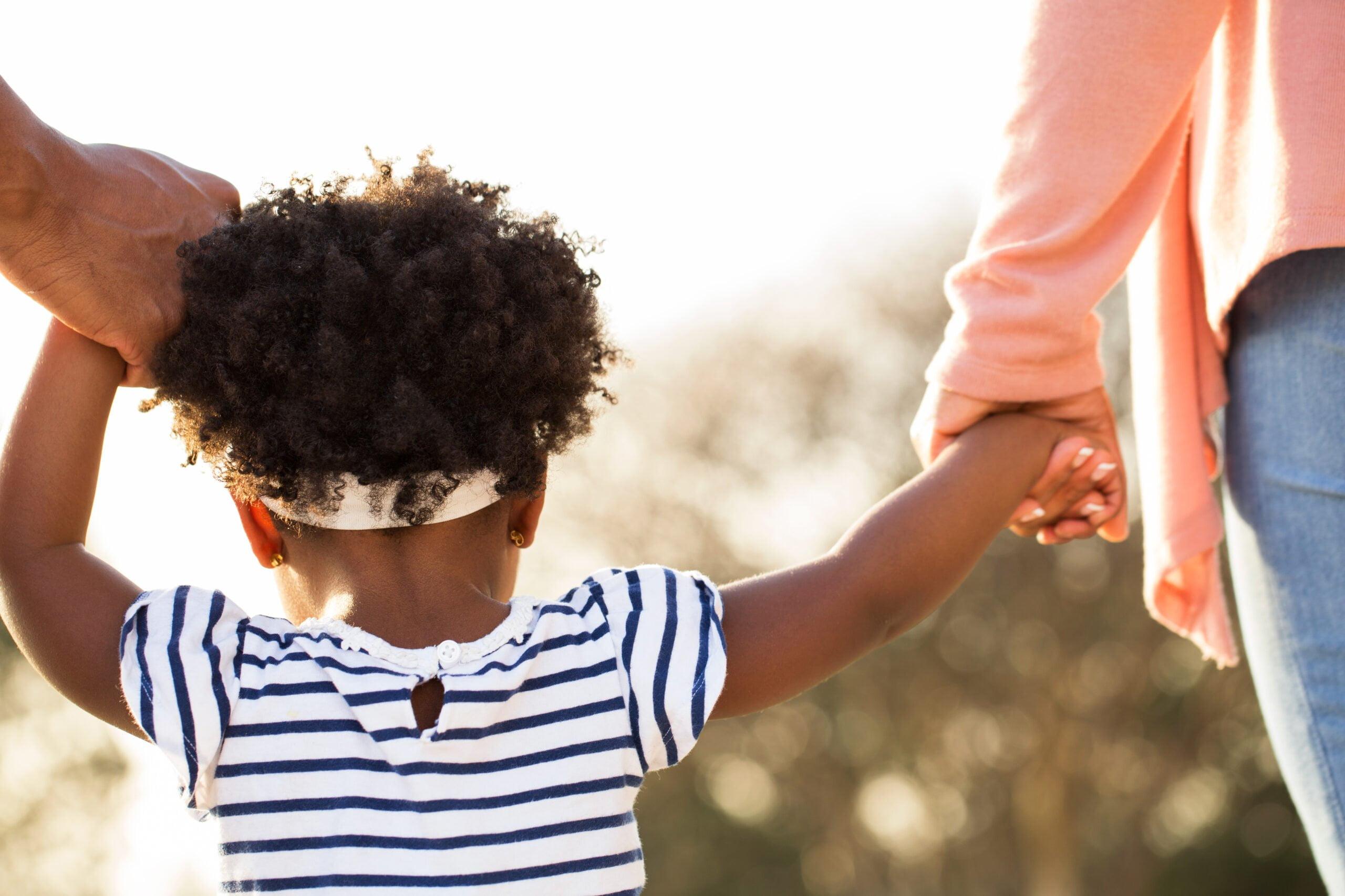 Foto mostra criança dando a mão para dois adultos