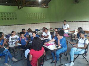 Foto mostra vários alunos reunidos em sala de aula