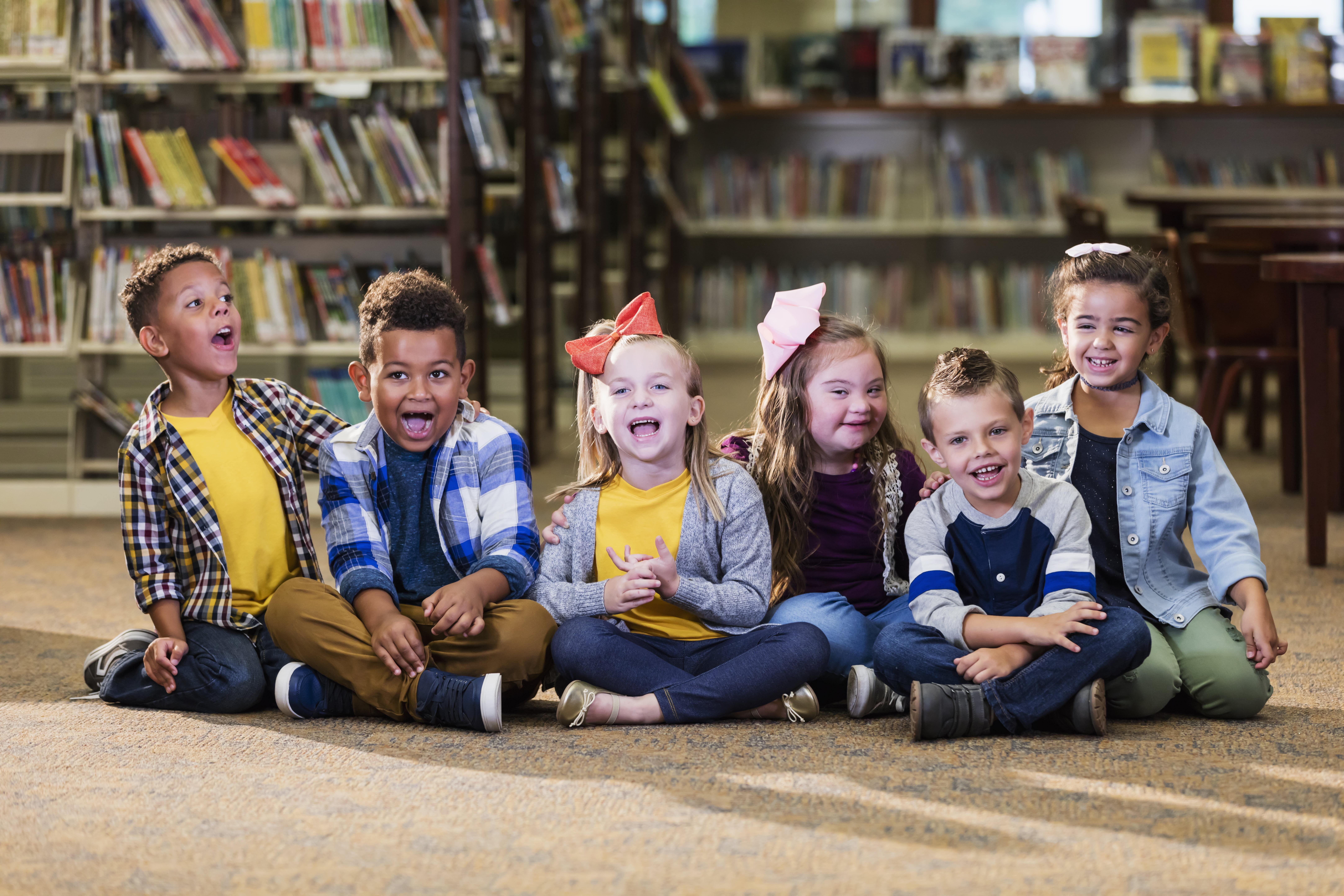 Foto mostra várias crianças sorrindo sentadas no chão da biblioteca de uma escola