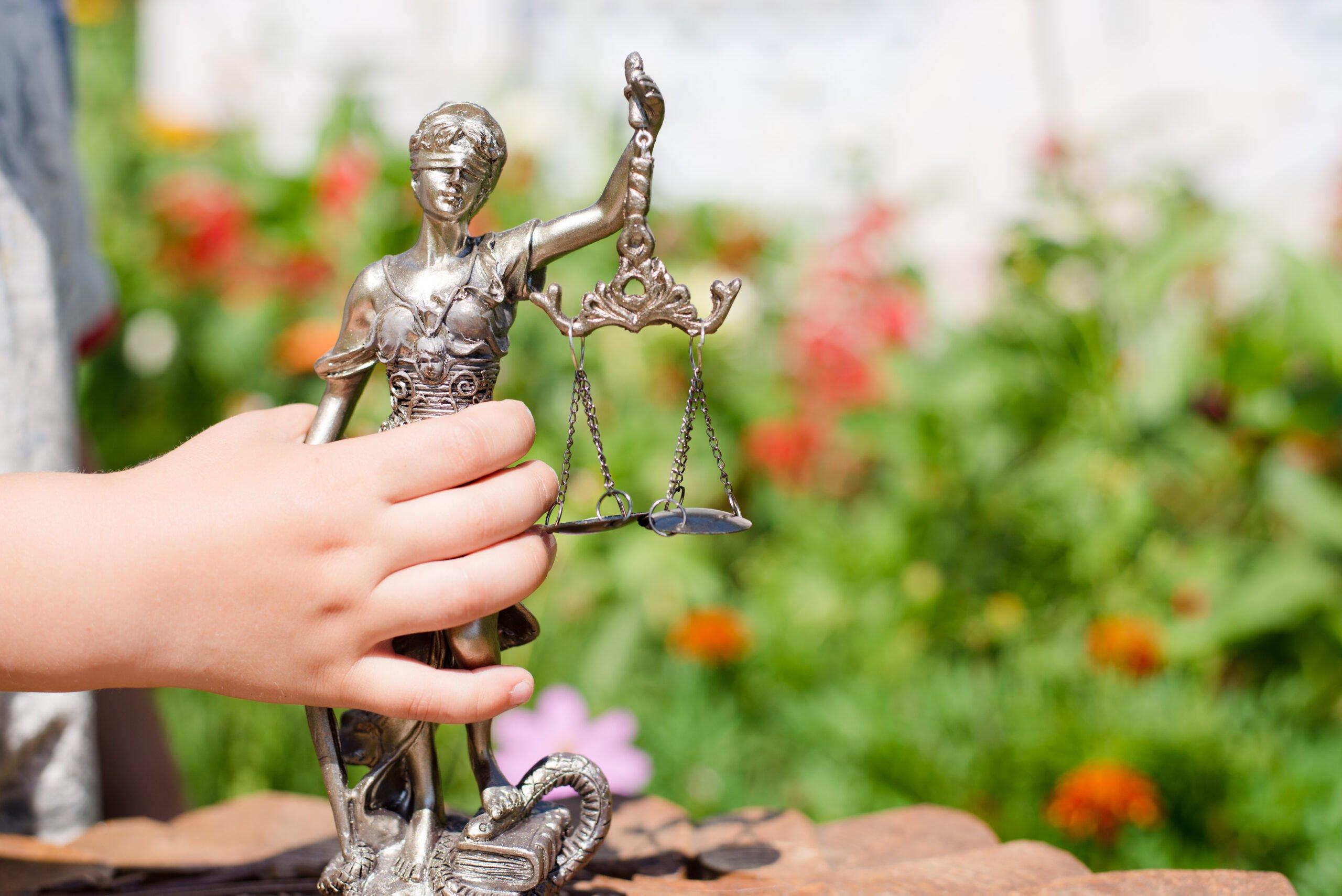 Foto mostra mão de criança segurando estátua da justiça