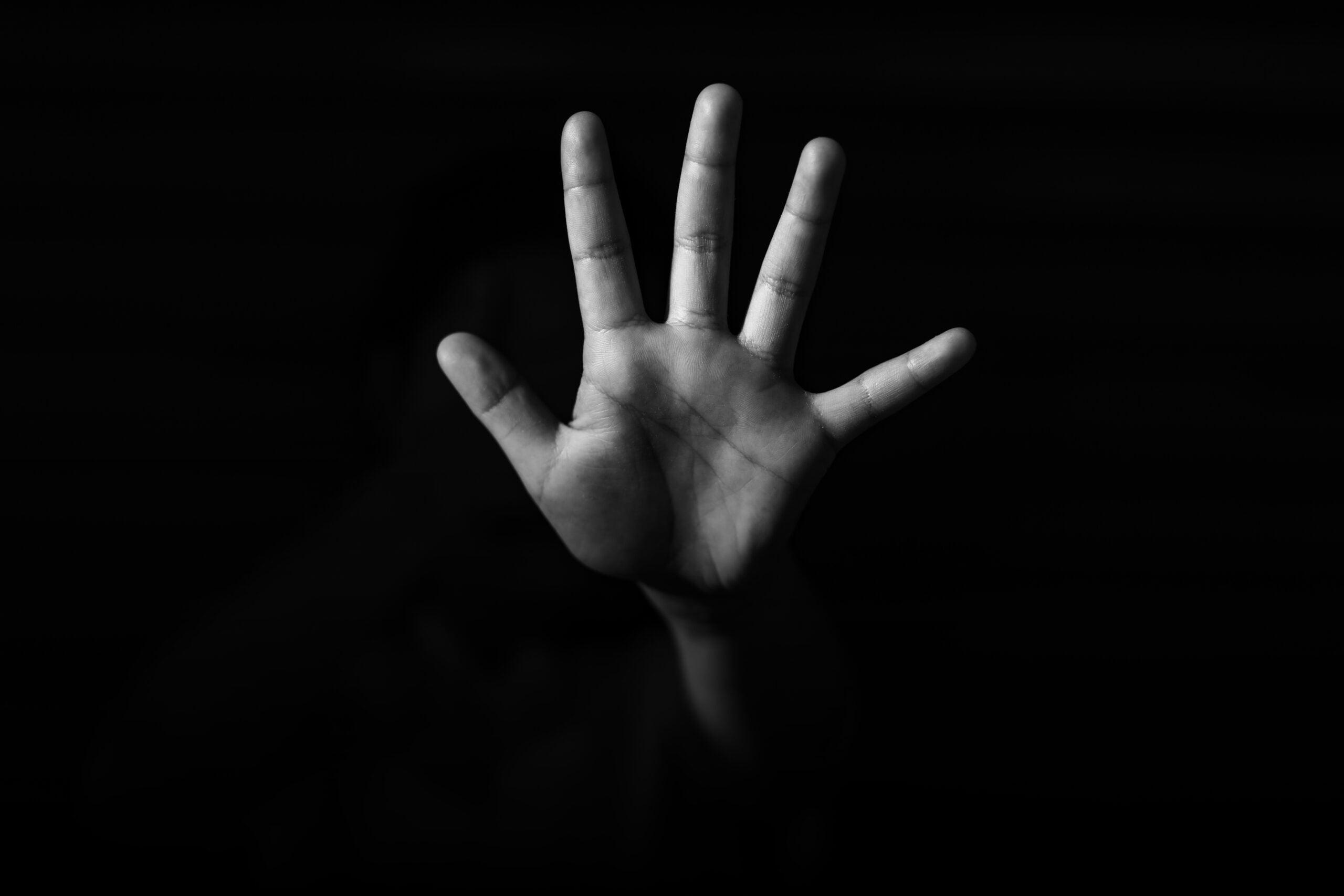 """Foto em preto e branco mostra mão aberta em sinal de """"pare a violência"""""""